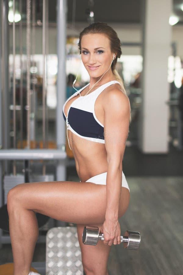 与金属哑铃的年轻人适合的妇女锻炼在健身房 库存图片
