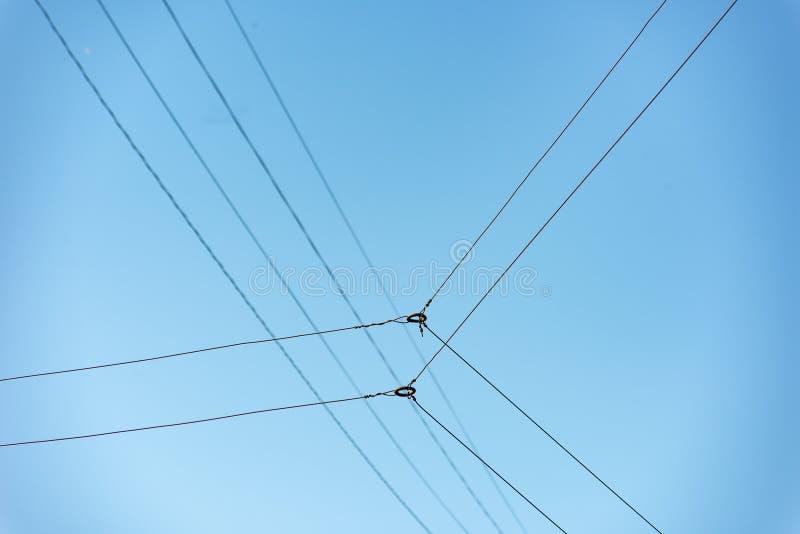 与金属圆环的相交的导线反对天空蔚蓝 图库摄影