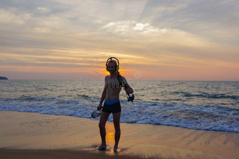 与金属探测器的寻宝人在日落海滩 免版税库存照片