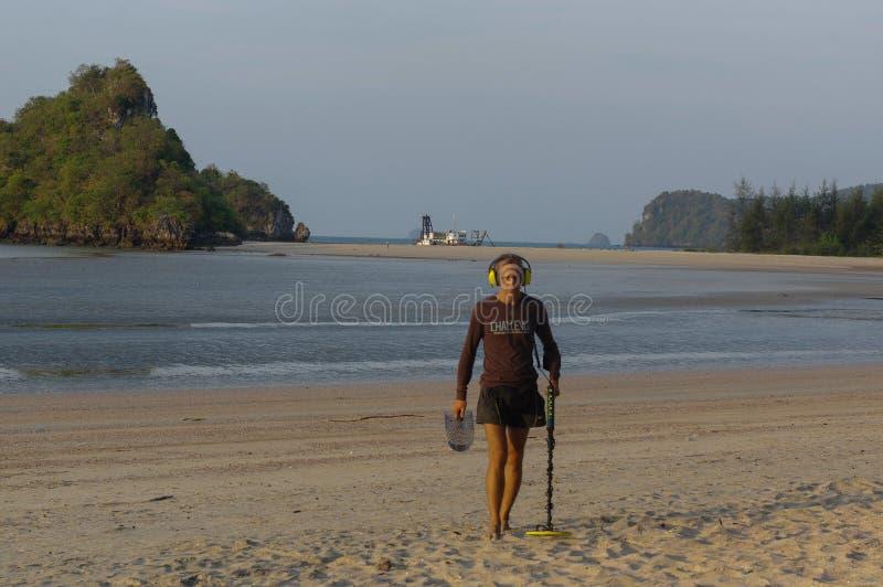 与金属探测器的寻宝人在海滩 库存图片