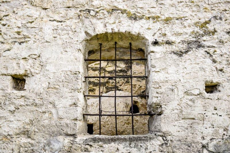 与金属棒的被成拱形的窗口在老石制品 古老半被破坏的犹太教堂 免版税库存图片