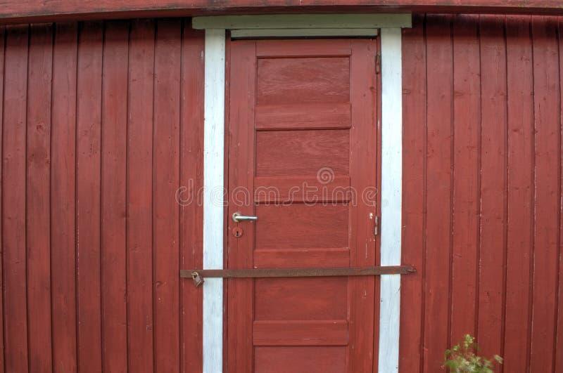 与金属棒螺栓锁的红色门 免版税库存图片