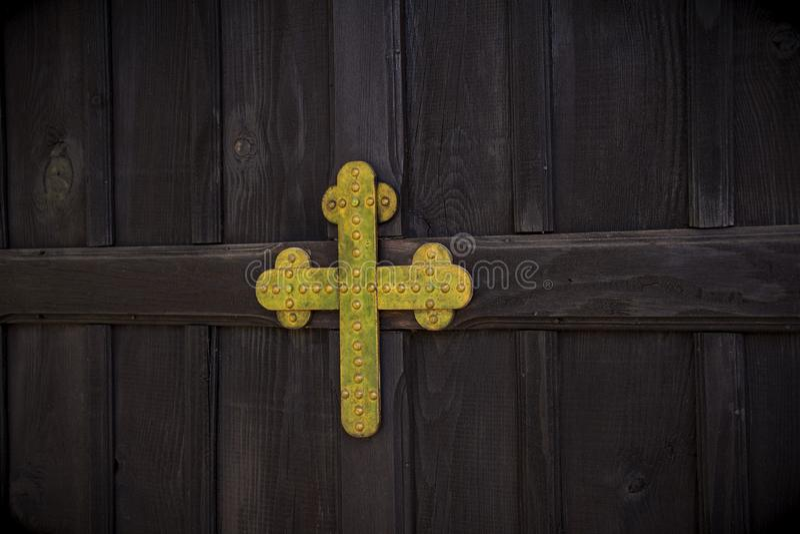 与金属金黄色的基督徒十字架的葡萄酒木门在基督教会里 库存图片