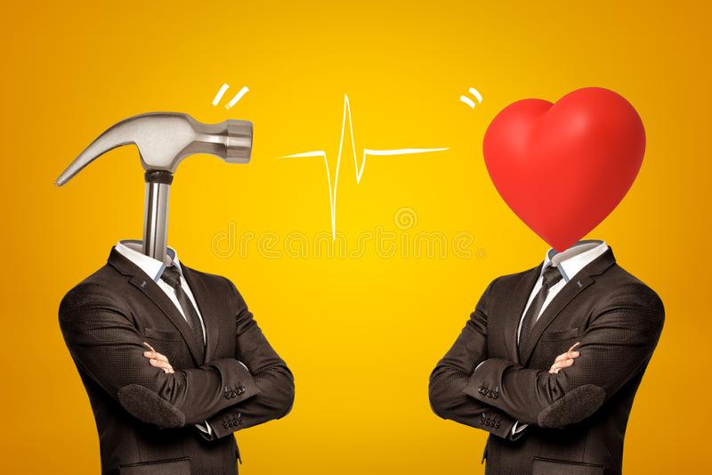与金属锤子和红心的两个商人而不是他们的在黄色背景的头 库存照片