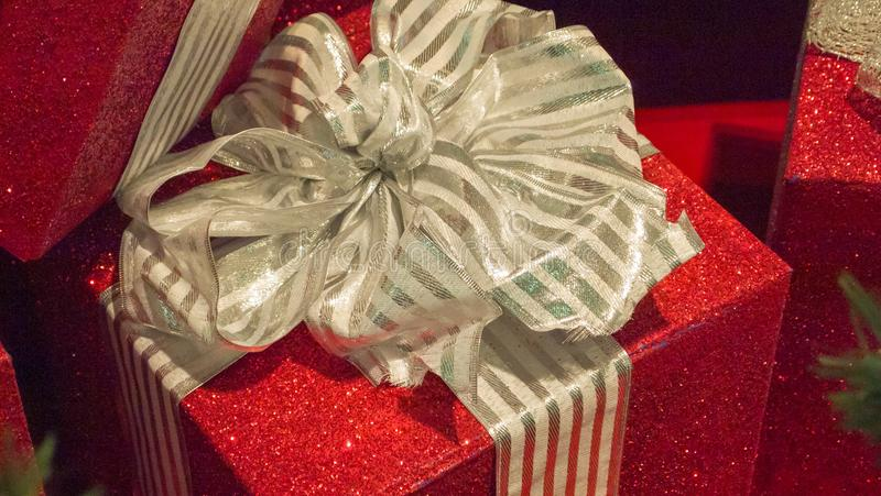 与金弓和丝带的特写镜头红色圣诞礼物 免版税库存照片