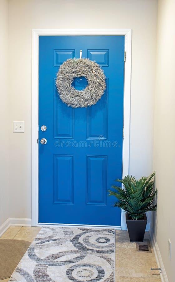 与金枝杈花圈的蓝色门 库存图片