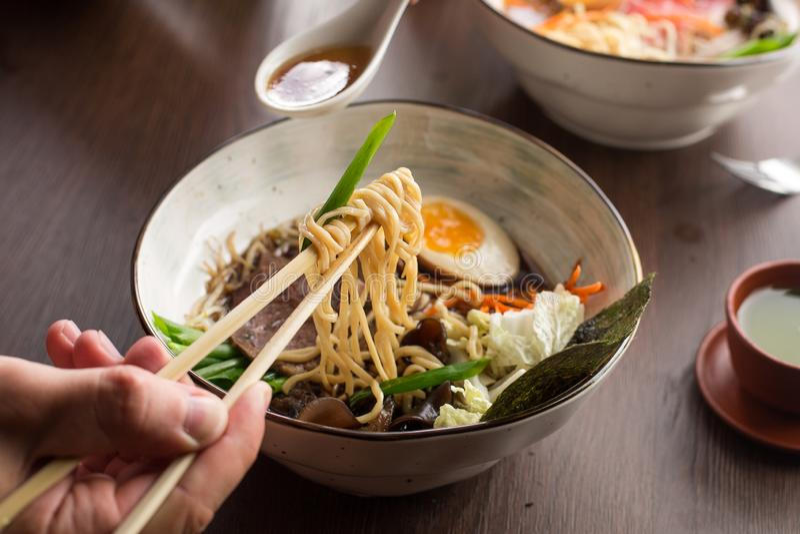 与金枪鱼和面条的食人的亚洲拉面在餐馆 免版税库存照片