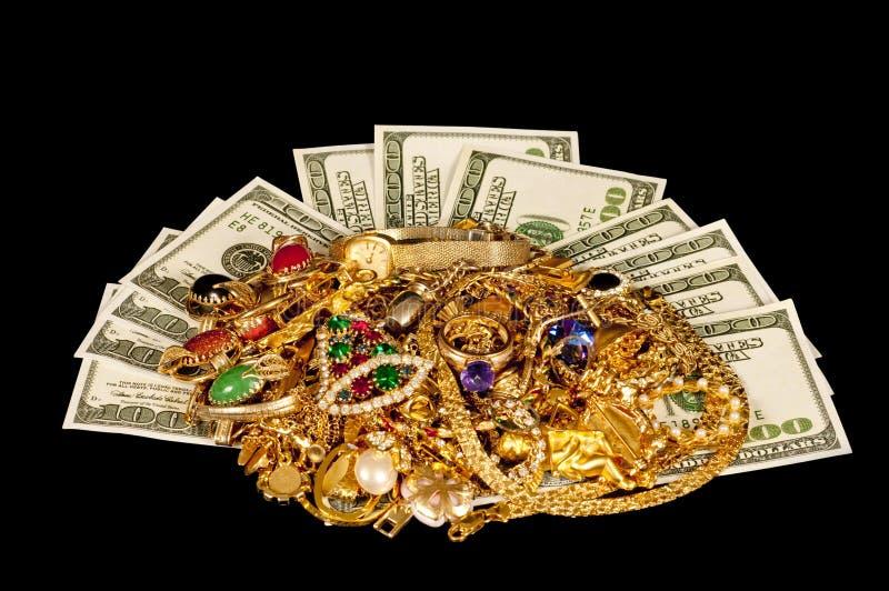 与金珠宝的现金在黑色布料背景 库存照片