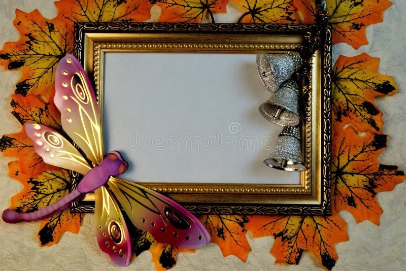 与金装饰品、蜻蜓和响铃背景的照片框架letterin的 免版税库存照片