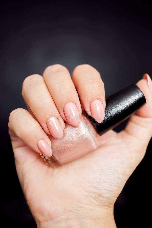 与金装饰的裸体修指甲 拿着一个瓶指甲油的妇女手 免版税库存照片