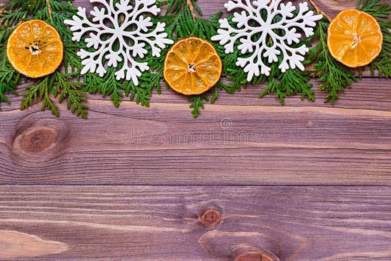 与金钟柏分支、雪花和蜜桔的圣诞装饰在木背景 库存图片