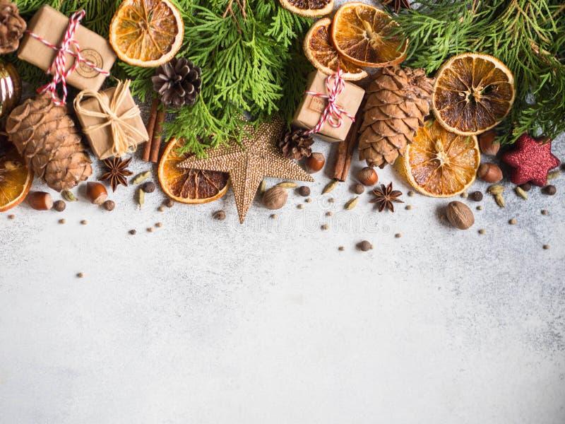 与金钟柏分支,圣诞装饰,香料,坚果,干橙色切片,杉木锥体的明亮的圣诞节或新年背景 免版税图库摄影