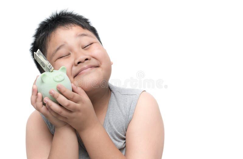 与金钱和存钱罐的愉快的肥胖男孩微笑 库存图片