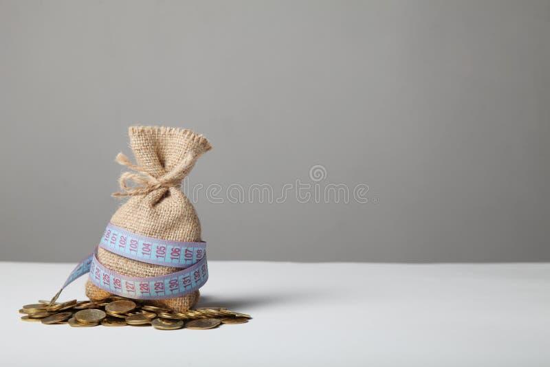 与金钱和测量的磁带的袋子在金币 缺钱、贫穷和储款 库存图片