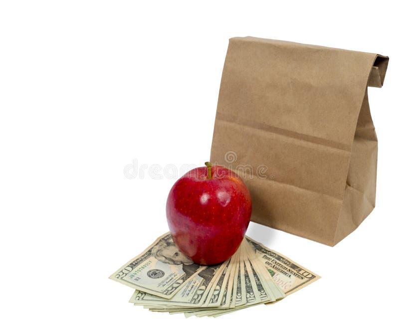 与金钱和红色苹果计算机的水平的布朗袋子 免版税库存图片