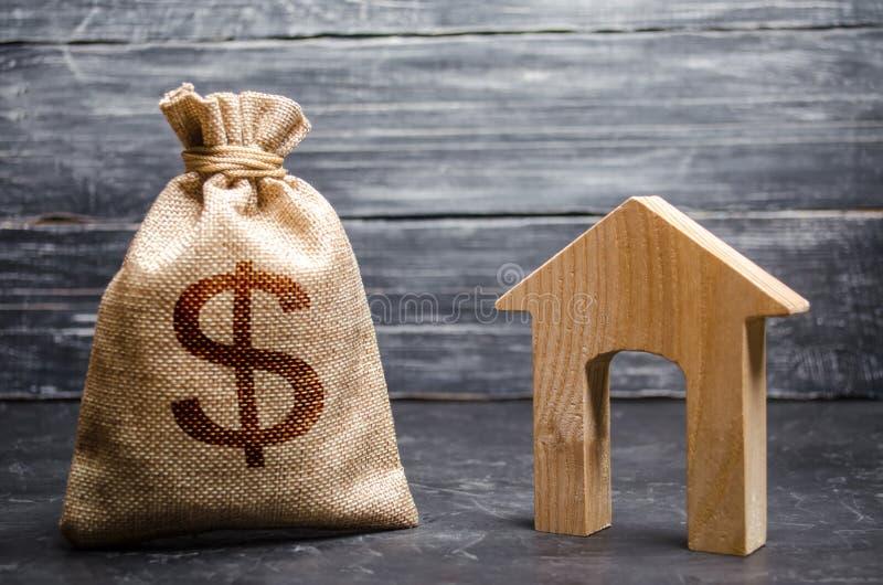 与金钱的一个袋子和有一个大门道入口的议院 不动产承购和投资的概念 付得起的便宜的贷款 库存图片