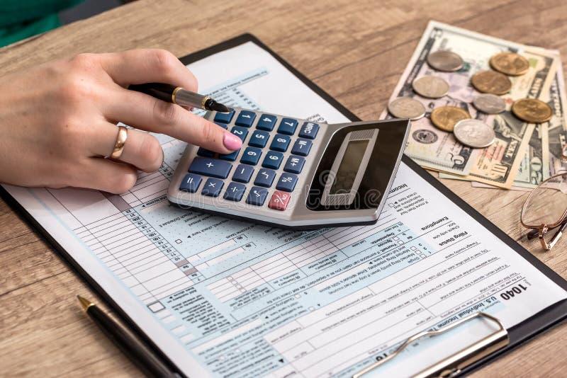 与金钱的妇女填装的报税表 库存图片