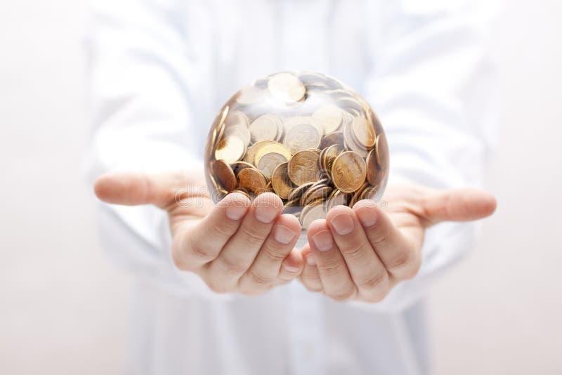与金钱的水晶球在手上 免版税库存图片