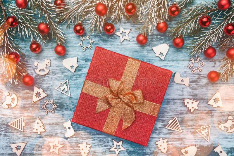 与金黄丝带的美丽的圣诞节礼物在与冷杉分支、红色中看不中用的物品和木玩具的蓝色背景 免版税图库摄影