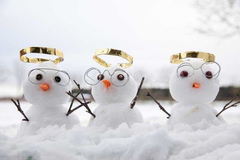 与金黄光晕的三个逗人喜爱的雪人角度 免版税库存照片