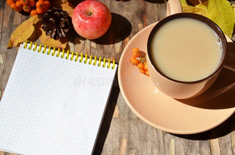 与金黄叶子的工作区,笔记本,咖啡杯 时髦的办公桌 秋天或冬天概念   库存照片