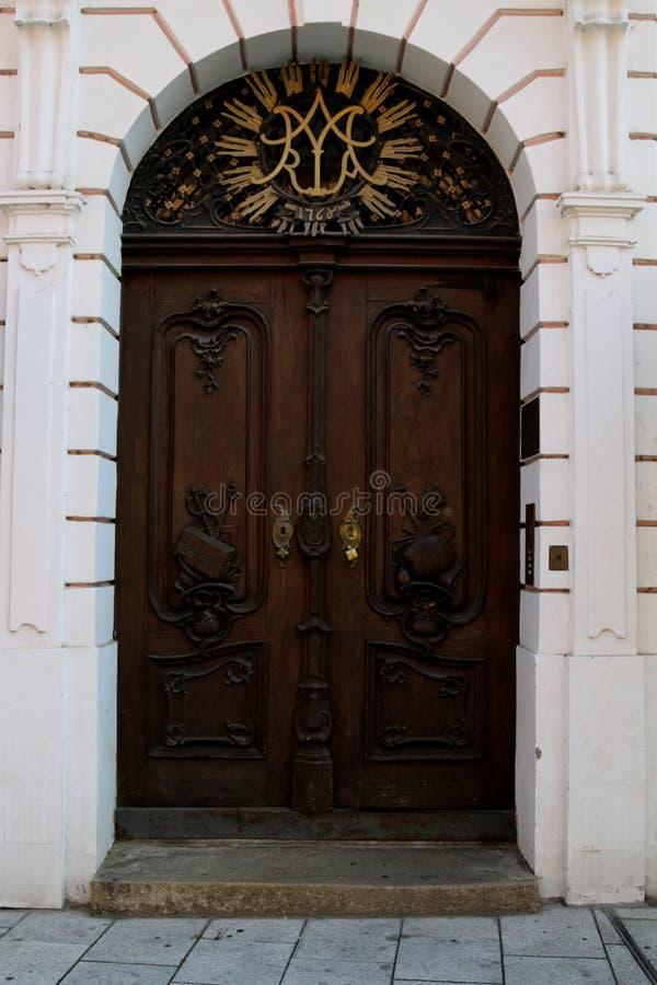 与金黄和黑金属元素的巴洛克式的棕色门在一个桃红色门面 免版税库存照片