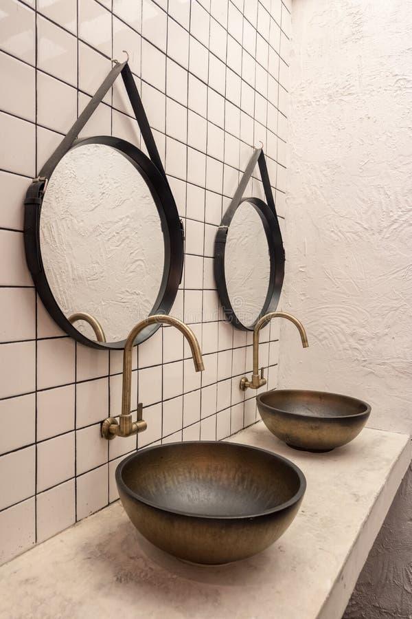 与金黄水龙头、老水槽和减速火箭的镜子的经典卫生间设计 库存照片