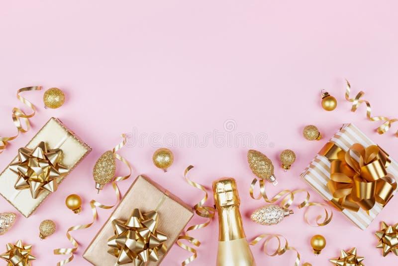 与金黄礼物的圣诞节背景或当前箱子、香槟和假日装饰在桃红色淡色台式视图 平的位置 图库摄影