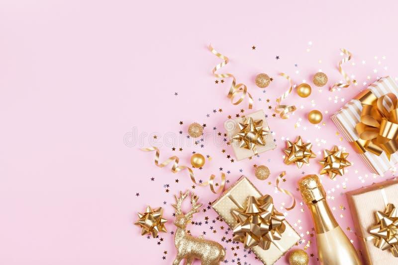 与金黄礼物的圣诞节背景或当前箱子、香槟和假日装饰在桃红色淡色台式视图 平的位置 免版税库存照片