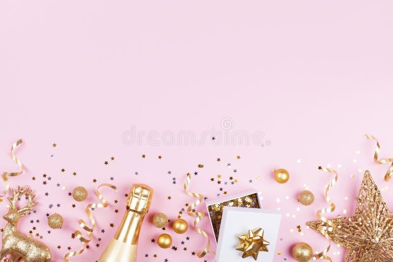 与金黄礼物的圣诞节背景或当前箱子、香槟和假日装饰在桃红色淡色台式视图 平的位置 免版税库存图片