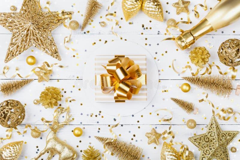 与金黄礼物的圣诞节背景或当前箱子、香槟和假日装饰在白色台式视图 2007个看板卡招呼的新年好 免版税库存照片