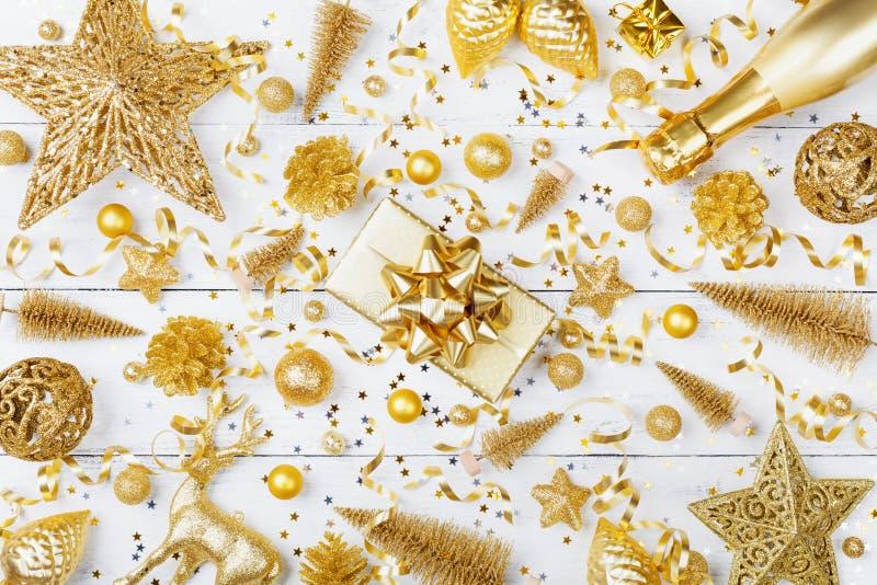 与金黄礼物的圣诞节背景或当前箱子、香槟和假日装饰在白色台式视图 平的位置 免版税库存照片