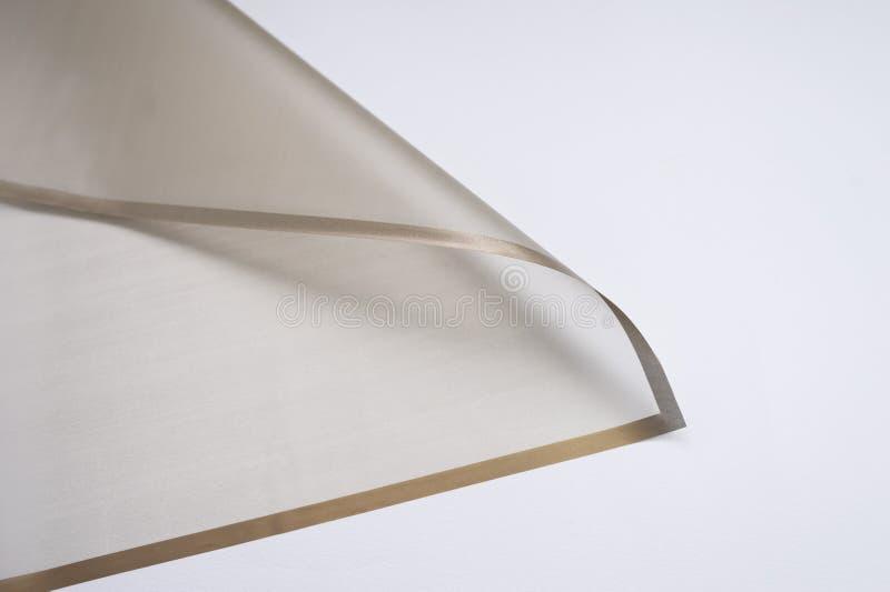 与金黄边缘的透明纸角落在白色背景 免版税库存照片