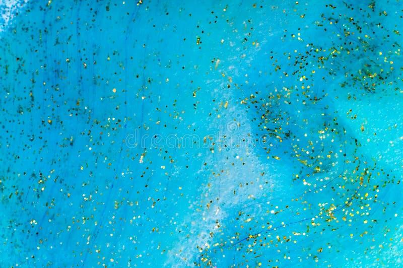 与金黄闪烁的背景透明软泥 库存照片