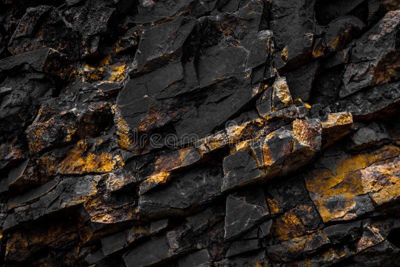 与金黄/黄色颜色的黑岩石背景 图库摄影