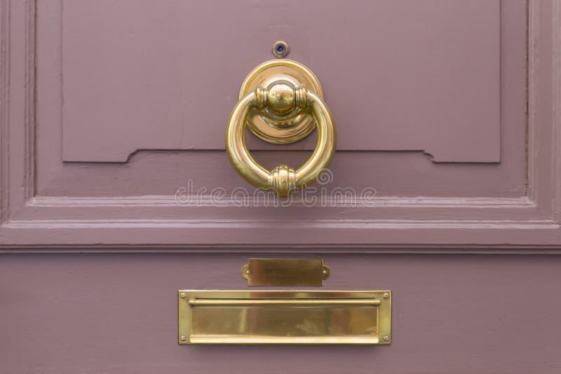 与金黄圆环和邮箱的桃红色木门 图库摄影