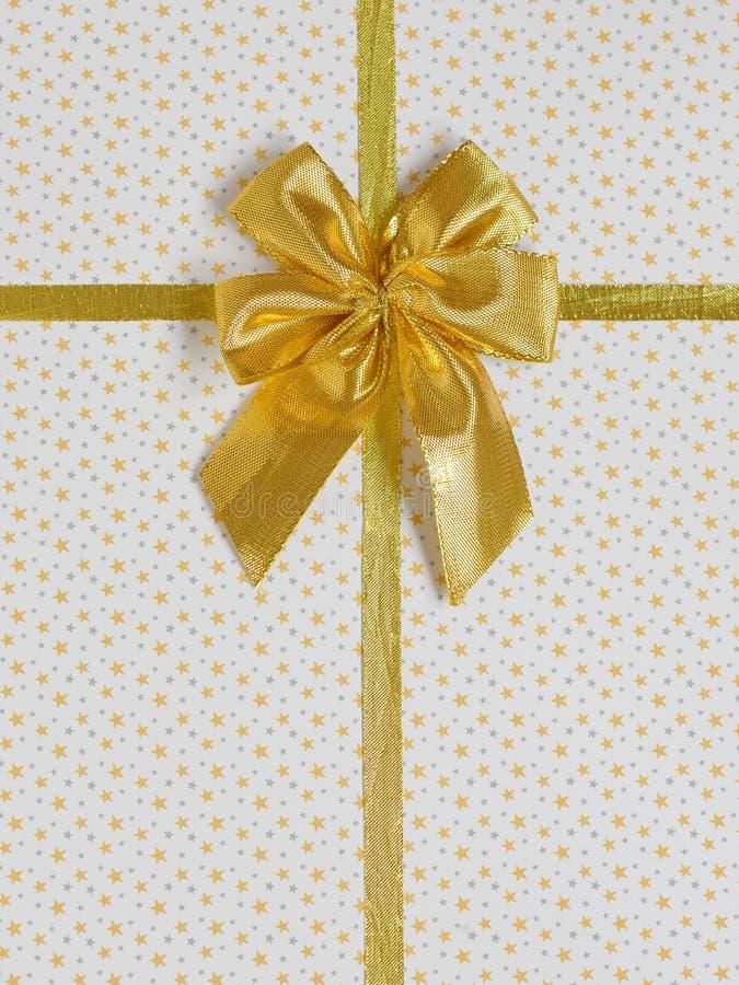 与金黄缎丝带的礼物弓 免版税库存照片