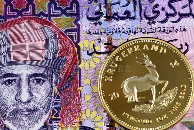 与金krugerrand硬币的五颜六色的一张阿曼里亚尔钞票 免版税库存照片