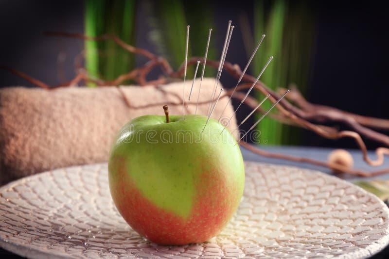 与针灸针的苹果计算机 免版税库存照片