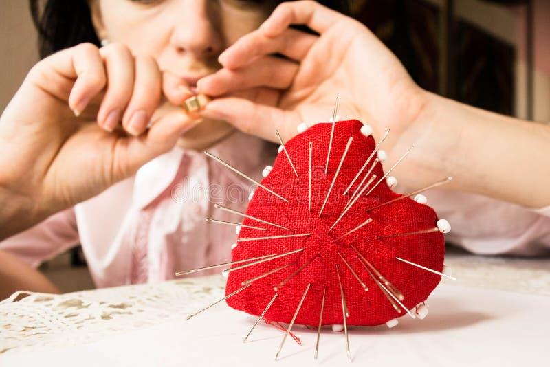 与针的红色心脏和有圆环的, selectiv年轻人生气妇女 库存照片