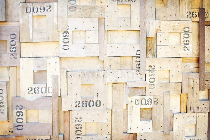 与钉子和钉书针的老棕色木纹理在方形的样式的墙壁上背景的,有数字 库存照片