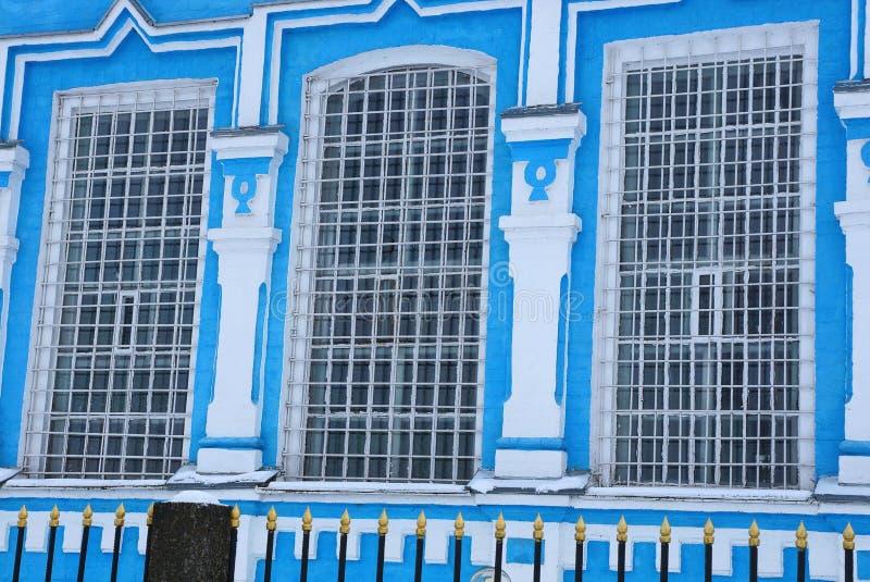 与钢棍的三个大老窗口在大厦的蓝色白色墙壁上在黑篱芭后的 免版税库存图片