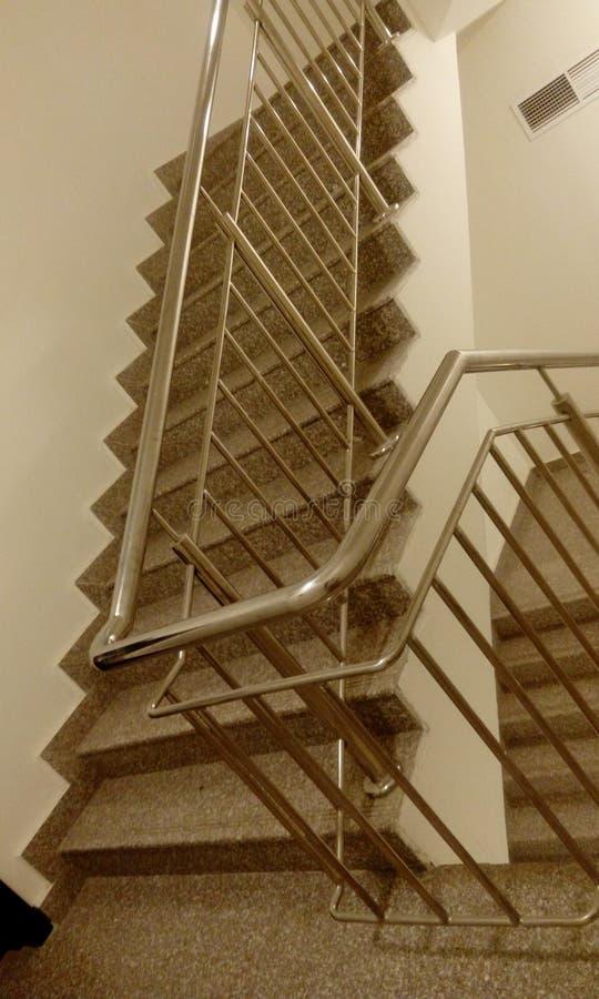 与钢楼梯栏杆的不锈钢扶手栏杆在从盖踩和造反者的midlanding的平板的高层商业大厦 免版税库存照片