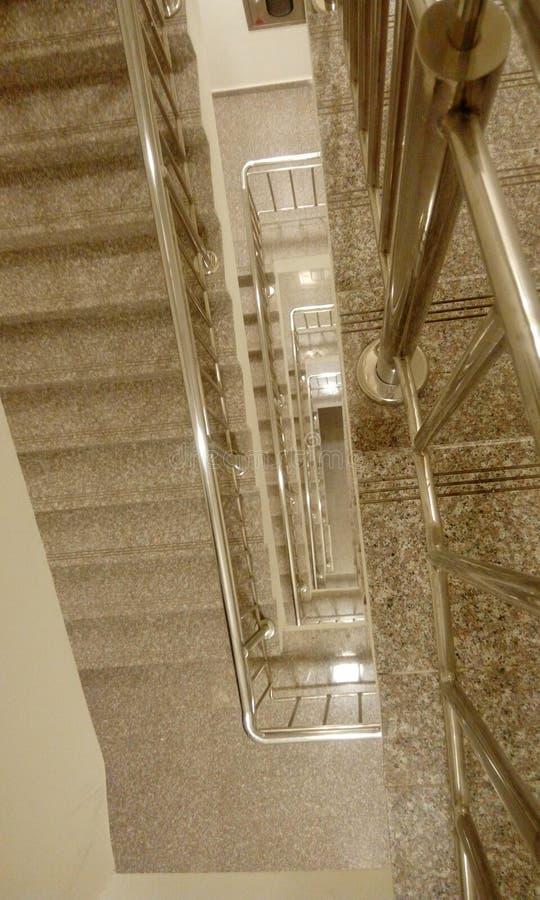 与钢楼梯栏杆的不锈钢扶手栏杆在从盖踩和造反者的midlanding的平板的高层商业大厦 免版税库存图片