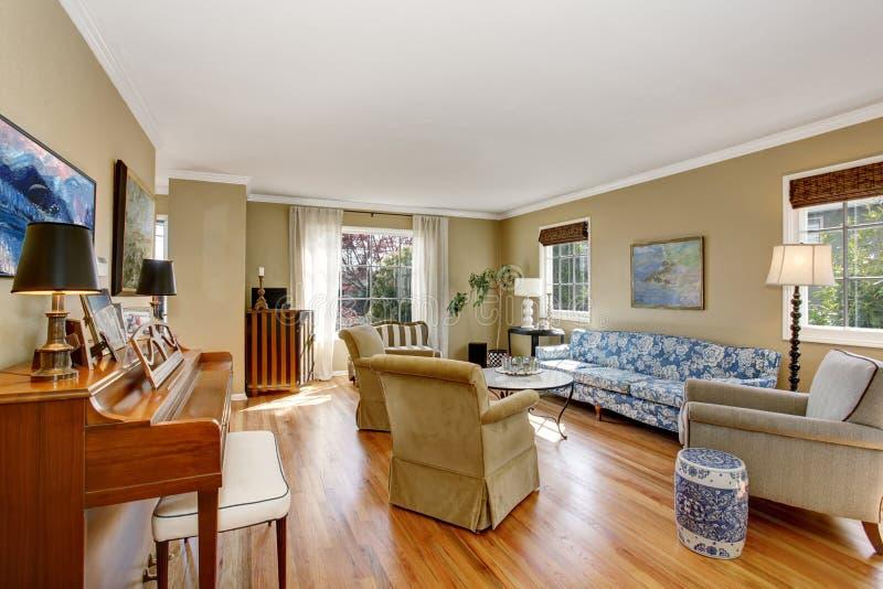 与钢琴、蓝色沙发和硬木地板的美国客厅内部 免版税库存照片