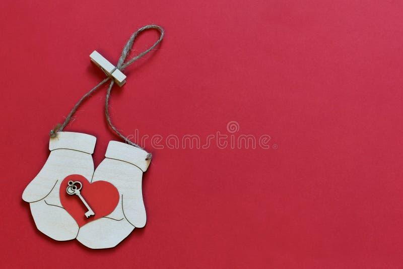 与钥匙的符号红心在黄麻麻线的葡萄酒手套与在明亮的红色背景的晒衣夹 简单派样式 库存照片