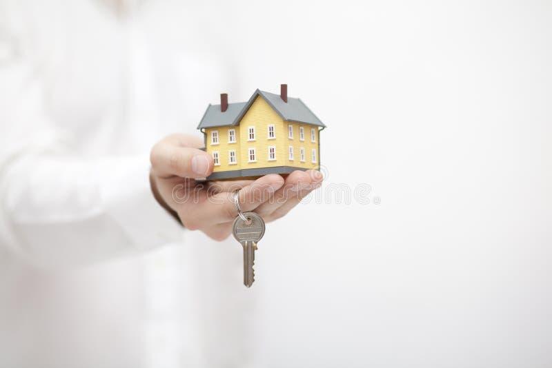 与钥匙的黄色房子缩样在手中 库存图片