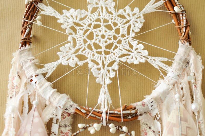 与钩针编织小垫布雪花的特写镜头细节手工制造dreamcatcher和在工艺纸背景的被绘的羽毛 库存照片