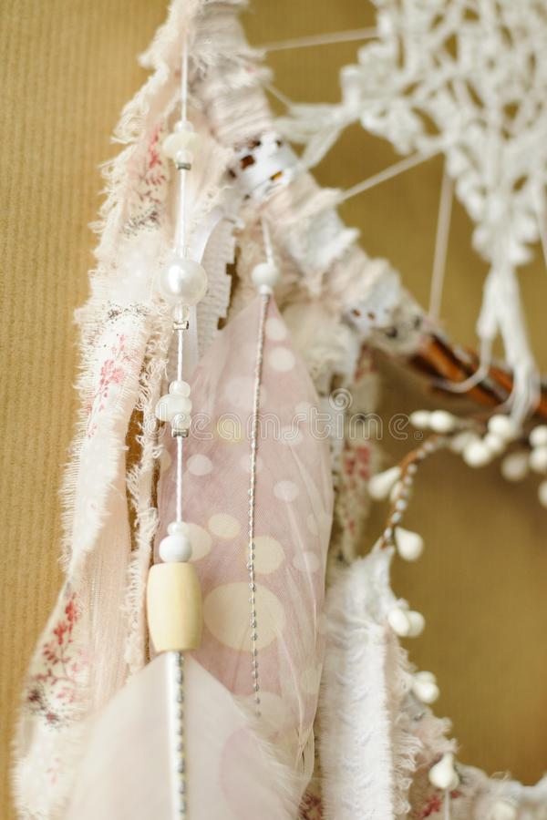 与钩针编织小垫布雪花的特写镜头细节手工制造dreamcatcher和在工艺纸背景的被绘的羽毛 免版税库存图片