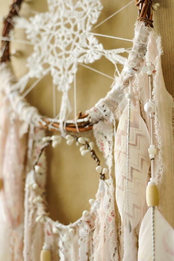 与钩针编织小垫布雪花的特写镜头细节手工制造dreamcatcher和在工艺纸背景的被绘的羽毛 免版税图库摄影